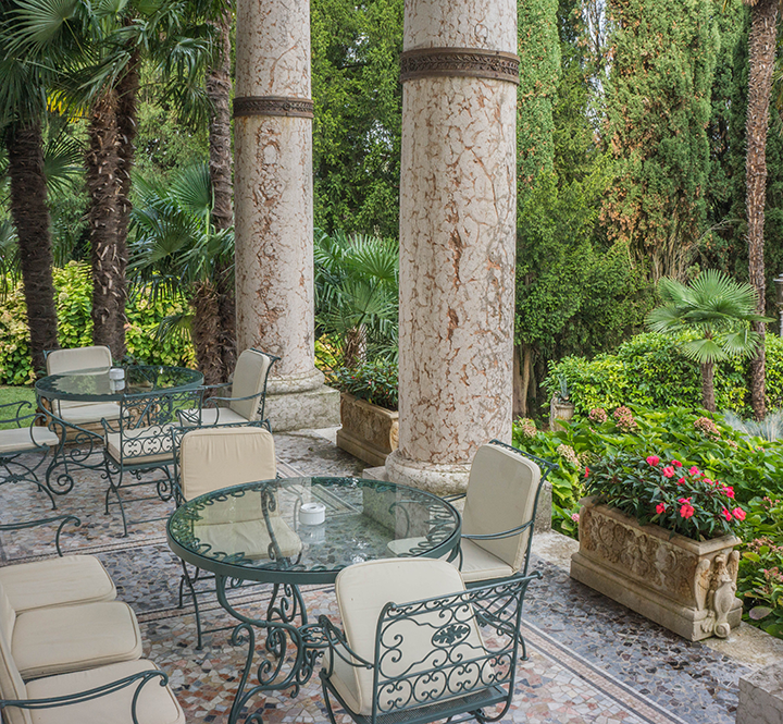 Patio at the Villa Cortine Palace Hotel in Sirmione, Italy. The building materials and details, furniture, and view each contribute to the biophilic experience of the space.